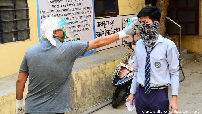 12th class students undergo thermal screening and sanitizing before attempt Mathematics paper in examination center, during the ongoing COVID-19 lockdown in Jaipur, Rajasthan