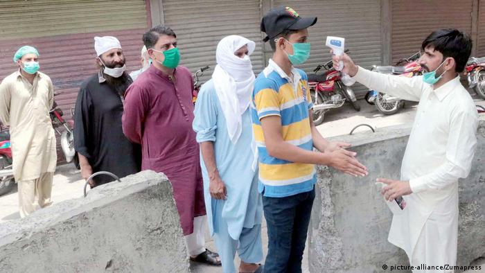 Health workers checks people's body temperature in Lahore city