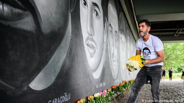 Brother of one of the victims lays down flowers at mural
