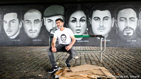 Cetin Gültekin, a brother of one of the victims of the Hanau attack, in front of a mural showing the victims