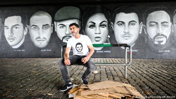 Arşiv - Hanau'daki ırkçı saldırıda hayatını kaybedenlerin resmedildiği bir panonun önünde, kurbanlardan Gökhan Gültekin'in abisi Çetin Gültekin (Frankfurt - 19.06.2020)