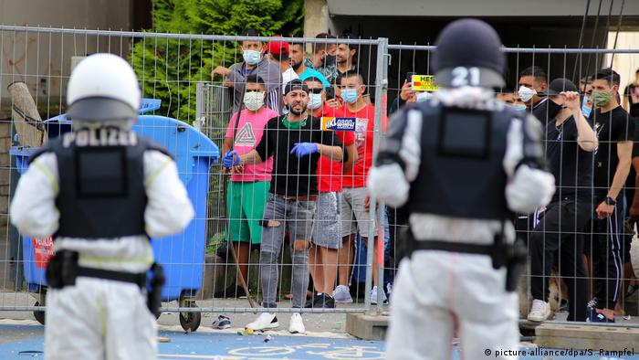 Police stand in front of a fence, behind which stands a group of quarantined people in Göttingen