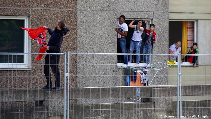 Local residents stand on a window ledge (picture-alliance/dpa/S. Rampfel)