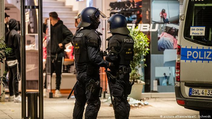 Policiais de capacete diante de loja vandalizada