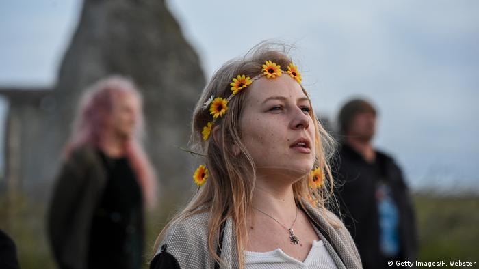 A woman participates in a ritual at Stonehenge as the sun sets ahead of Summer Solstice on June 20, 2020 in Amesbury, United Kingdom.