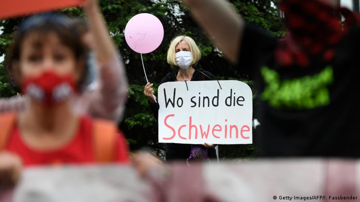 A protestor holds a sign that reads 'where are the pigs?' in front of the headquarters of German abattoir company Tönnies