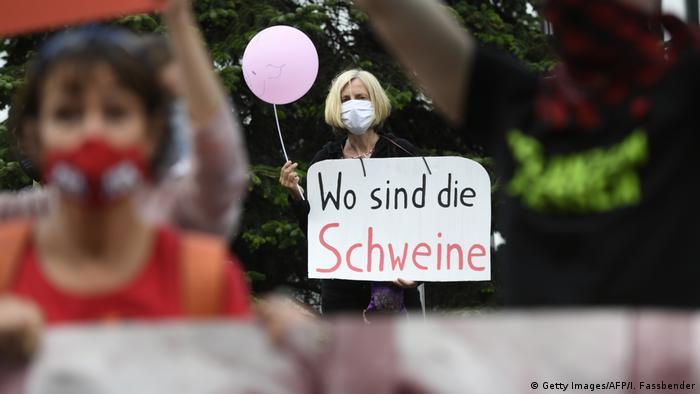 Eine Demonstrantin hält ein Schild mit der Aufschrift Wo sind die Schweine? hoch