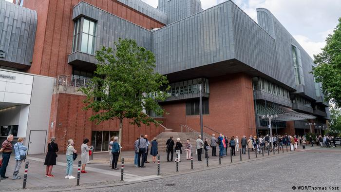 People stand in line outside the red brick and steel modern structure, the philharmonic concert hall in Cologne