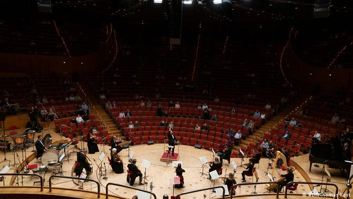 Musicians spread out on the semicircular stage, conductor with arm raised at center, small clusters in the mostly unoccupied seats in front of them in the Cologne Philharmonie