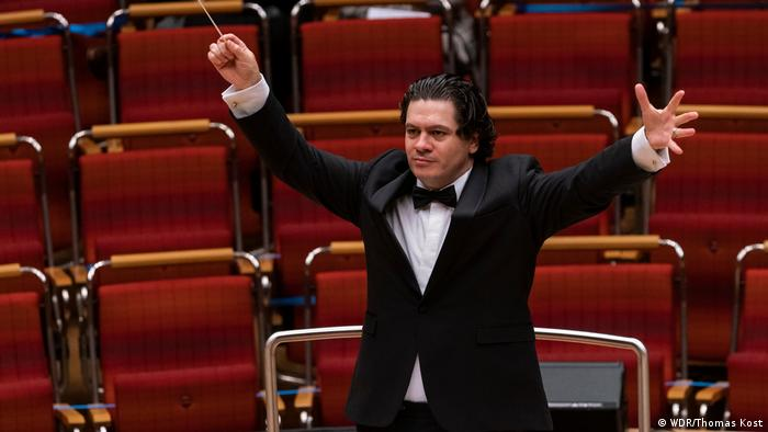 Rumanian-born conductor Christian Macelaru, baton in hand, stretches his arms wide