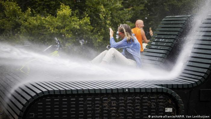 A woman is sprayed with water cannon
