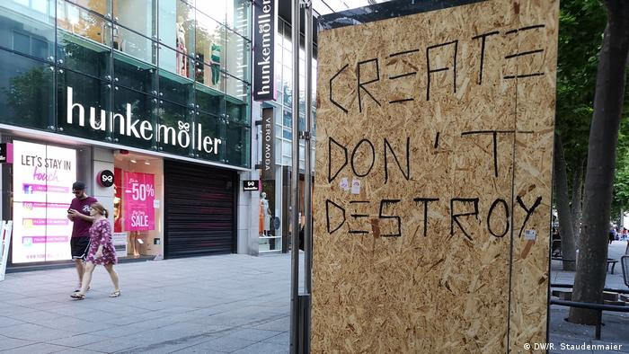 A sign reading 'create don't destroy' boarding up a broken window