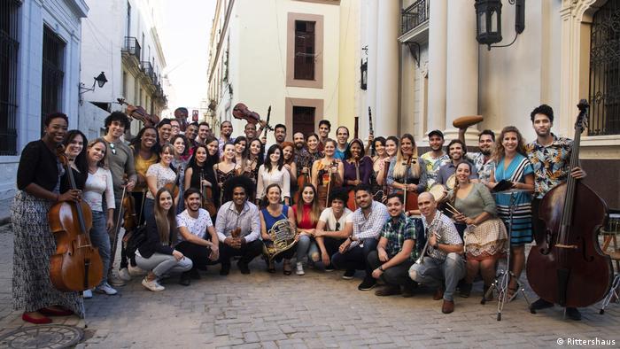 Sarah Willis und das Orquesta del Lyceum de La Habana posieren mit ihren Instrumenten in einer Straße in Havanna, Kuba.