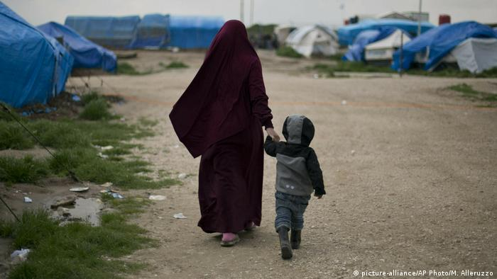 A Syrian woman holds her child's hand as they walk through a refugee camp in northern Syria
