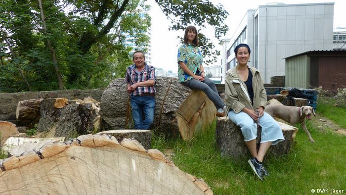 Drei Stadtgärtner aus Wuppertal sitzen auf Baumstämmen