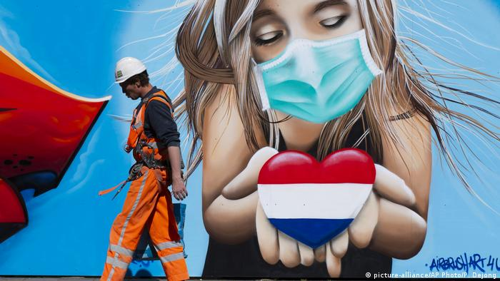 A large mural of a blonde girl wearing a mask and holding a heart-shaped Dutch flag.