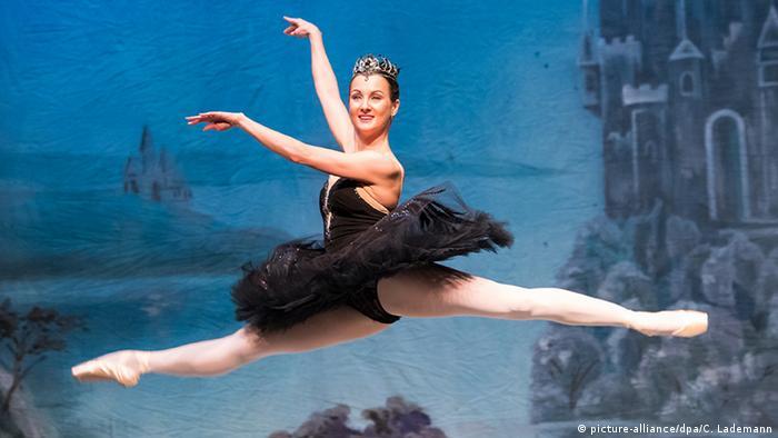 Eine Tänzerin vom weißrussischen Bolschoi Ballett führt in der Rolle des schwarzen Schwans in Schwanensee einen Spagatsprung aus