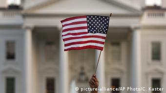 Американский флаг в поднятой руке на фоне Белого дома