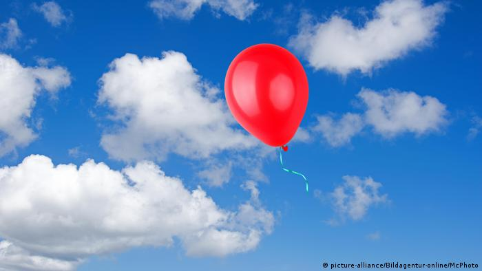 Red balloon floating through a blue sky scattered with clouds.