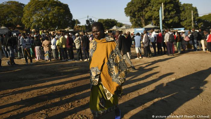 People stand in a line as they wait to vote in Malawi's elections.