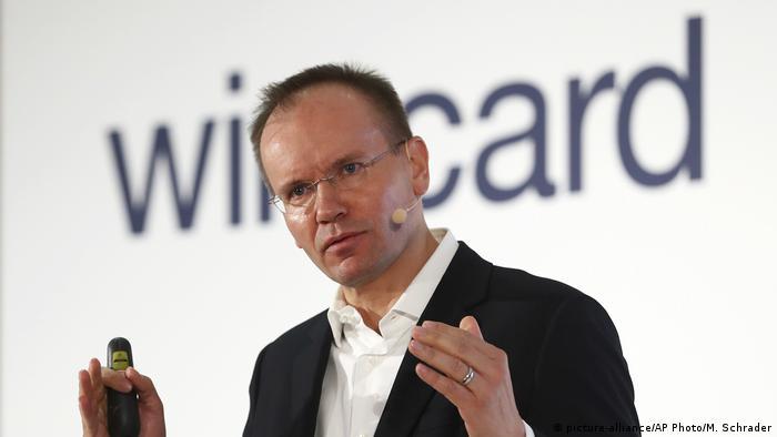 Der ehemalige Wirecard-CEO Markus Braun mit Headset bei einer Rede, im Hintergrund ist etwas verschwommen die Aufschrift wirecard zu sehen (picture-alliance/AP Photo/M. Schrader)