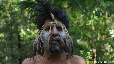 An indigenous Australian wears a traditional mask made of twisted twine and dark feathers that fall across his face. His cheeks and the bridge of his nose are painted white.
