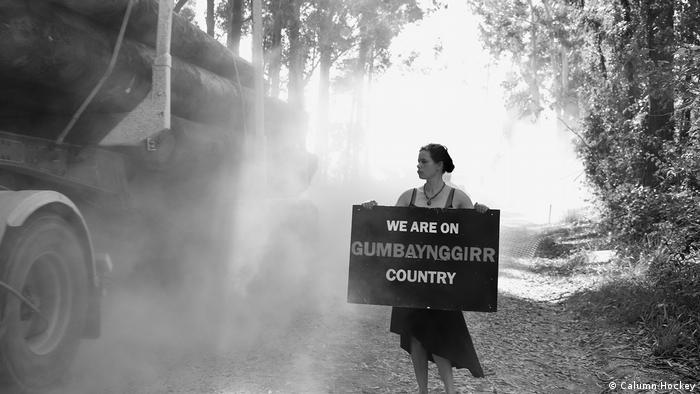 A black and white photo of a woman holding a sign that says We are on Gumbaynggirr country