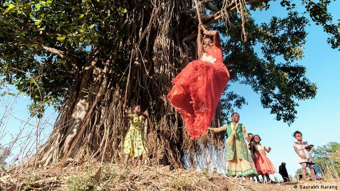 A group of young Siddi girls play at an old tree in their village of Mainalli, taking swings from its branches.