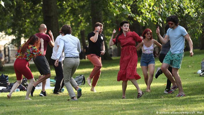 Mit einem Tänzchen im Londoner St. James's Park reagieren diese jungen Leute auf die Abmilderung der Beschränkungen (Foto: picture-alliance/empics/Y. Mok)