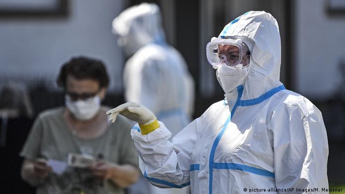 Медицинский работник в белом защитном костюме