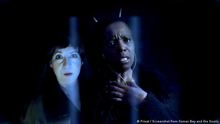 Im Vordergrund steht eine Person mit Ohrstöpseln im Ohr, im Hintergrund eine weiß Geschminkte - angedeutete Gitterstäbe sind ganz vorn zu sehen (Foto: privat / Screenshot von Osman Bey and the Snails)