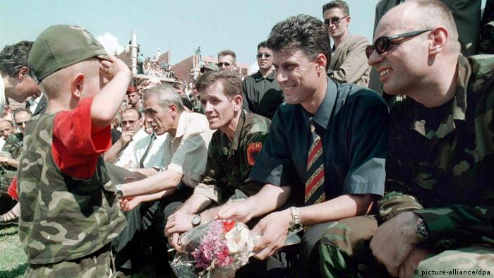 An Albanian boy in military uniform salutes KLA leader Hashim Thaci (2nd R) during Albanian celebrations marking the retreat of Serbian troops from Podujevo, Saturday, 07 August 1999.