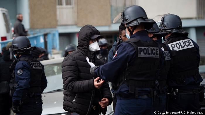 olice officers wearing protective masks control people during an anti-drug operation in the Cite des Oliviers, a northern neighbourhood of Marseille