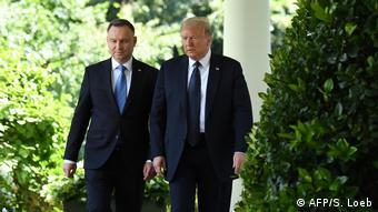 Donald Trump e Andrjei Duda de paletó escuro e camisas brancas no jardim da Casa Branca