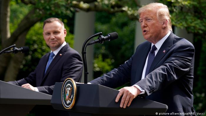 Links im Bild lächelt ein braunhaariger Mann im Anzug hinter einer Rednertribüne und einem Mikrofon, rechts spricht ein blonder, älterer Mann im Anzug in eine Mikrofon, vor ihm steht ebenfalls eine Rednertribüne