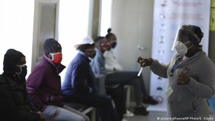 Medical worker with mask in Soweto hospital with masked patients (picture-alliance/AP Photo/S. Sibeko)