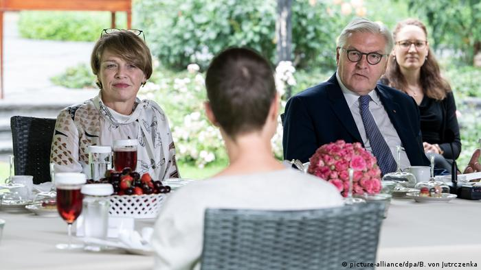 German president frank Walter Steinmeier sits outside at a table with his wife