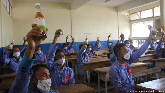 Мадагаскарские школьники поднимают вверх бутылки с настойкой полыни