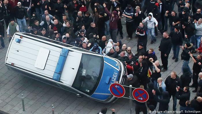 Köln | Demonstranten werfen Polizeiauto um