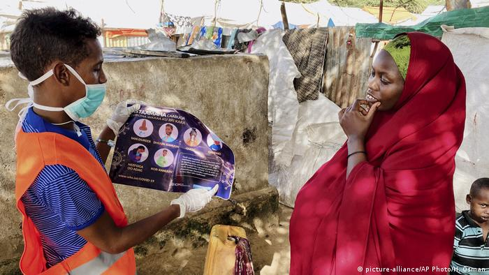 SA health worker explains to an internally-displaced Somali woman in Mogadishu how to protect herself from coronavirus (picture-alliance/AP Photo/H. Osman)