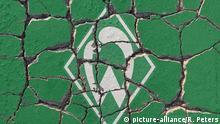 der Traditionsclub und Deutscher Meister vergangener Tage, Werder Bremen, hat in der 1. Fußball Bundesliga einen Fehlstart erwischt. Vereinsemblem auf erodierendem Straßenpflaster. | Verwendung weltweit