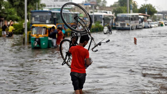 Indian man walking with a bicycle through flooded street