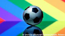 Symbolbild Homosexualität im Sport Fussball liegt vor Regenbogenflagge