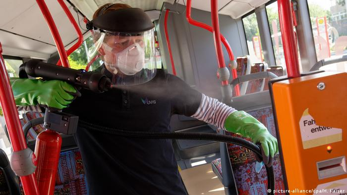 Man in mask and protective gear sprays bus surfaces