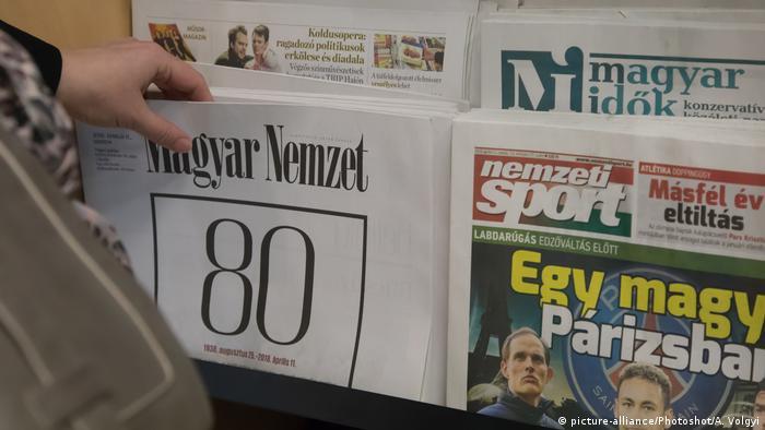 A person picks up a newspaper from a Hungarian newsstand