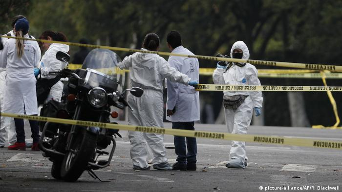 A forensics team scourt a cordoned-off area (picture-alliance/AP/R. Blackwell)