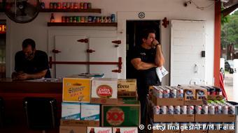 На входе в бар выставлены напитки и стоит брат хозяина бара