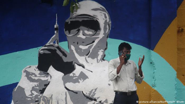 A man talks on a mobile phone in front of a mural in tribute to frontline workers during the COVID-19 pandemic in Mumbai