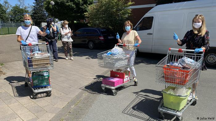 Volunteers give a thumbs up as they prepare to wheel trollies filled with aid