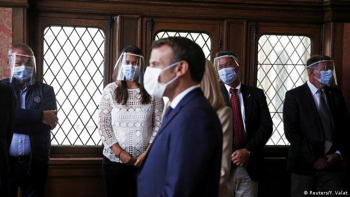 A masked Macron casts his ballot in front of other masked people